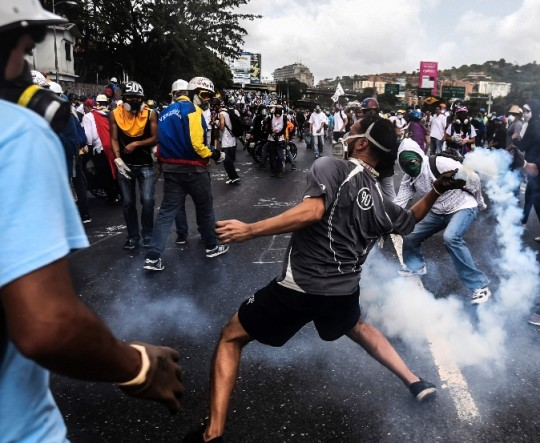 Riot police clash with opposition demonstrators during a protest in Caracas, on May 24, 2017. Venezuela's President Nicolas Maduro formally launched moves to rewrite the constitution on Tuesday, defying opponents who accuse him of clinging to power in a political crisis that has prompted deadly unrest. / AFP / JUAN BARRETO